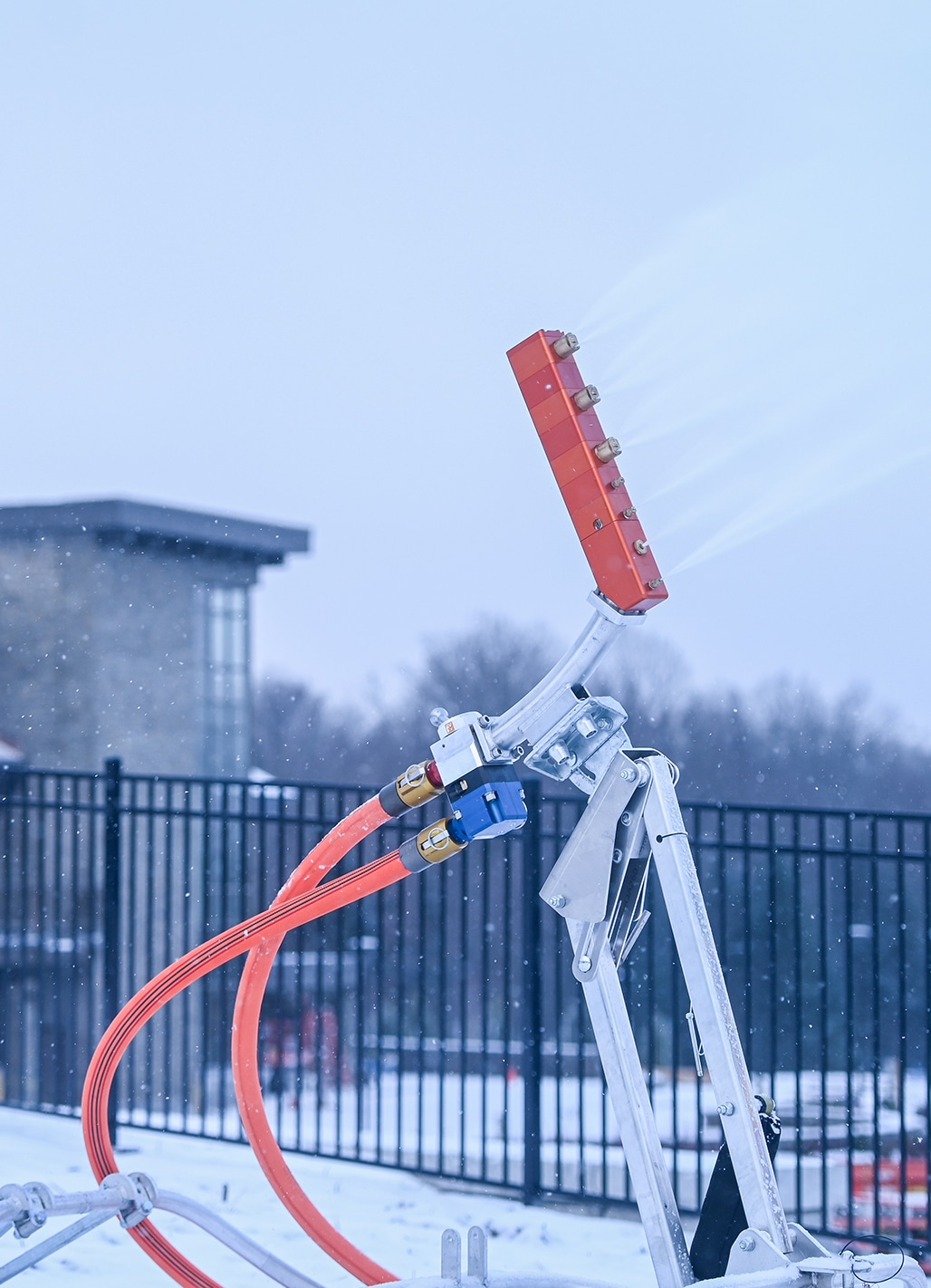 A snow making machine shoots snow at one of the venues for the Games