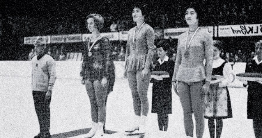 Black and white historical photo of female figure skaters on a medal podium from previous Games.