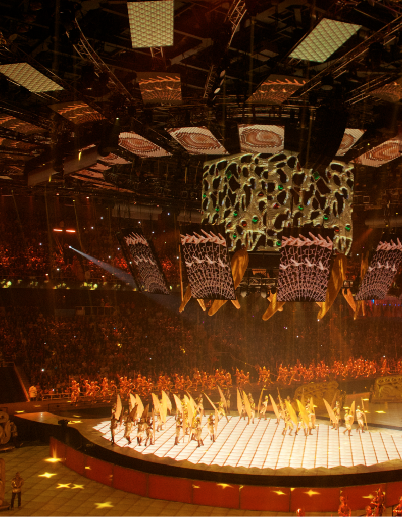 A large group holding yellow flags performs during a previous Winter Games opening ceremony